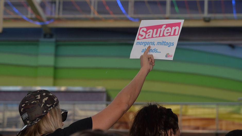 """Eine Partygängerin im Megapark auf Mallorca hält ein Schild mit der Aufschrift """"Saufen"""" hoch."""