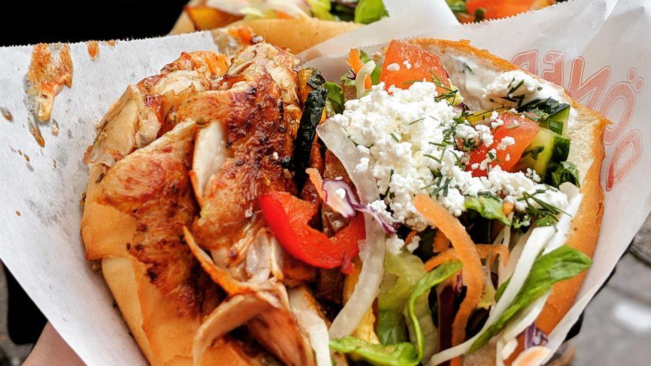 Eine Dönertasche gefüllt mit Fleisch, Gemüse und Käse.