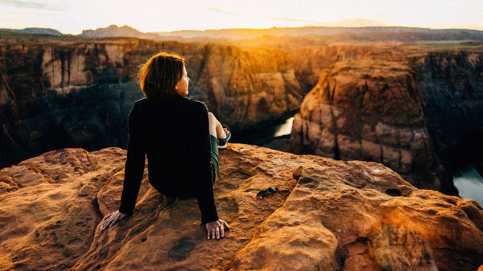 Frau sitzt an einem Canyon bei Sonnenuntergang.