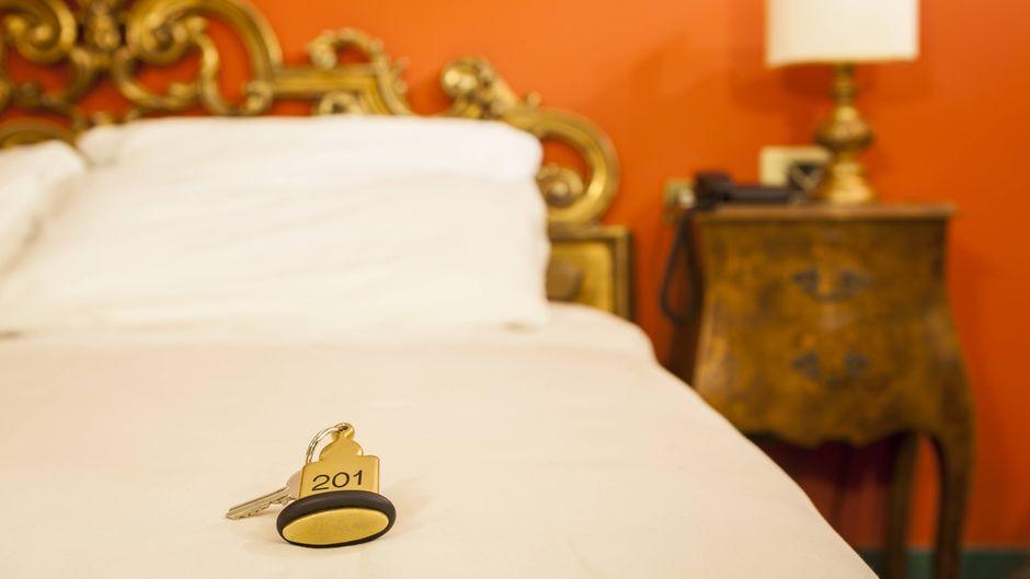 Hotelschlüssel liegt auf einem Bett im Hotelzimmer