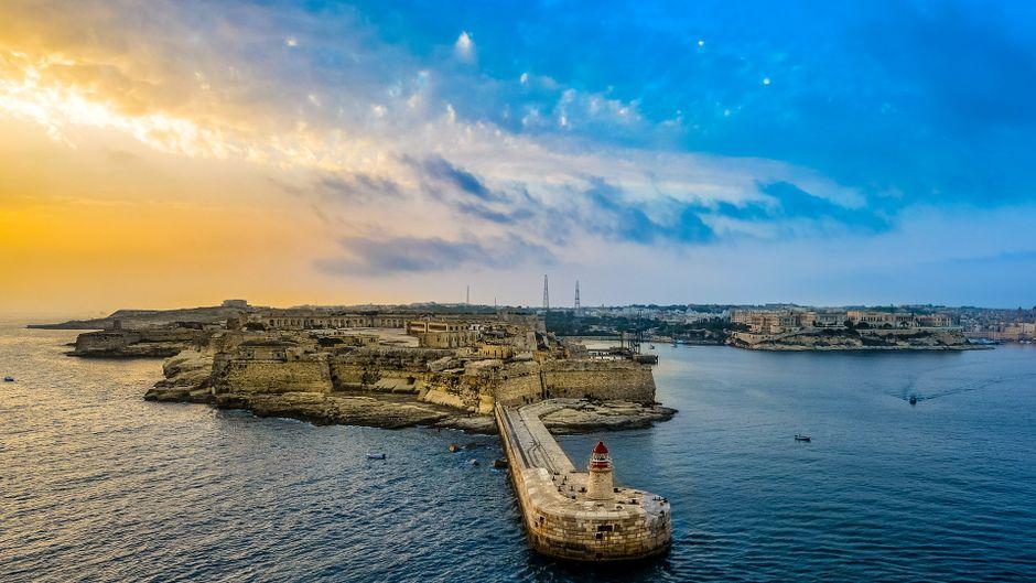 Leuchtturm und Hafen von Valletta (Malta) bei Sonnenaufgang.