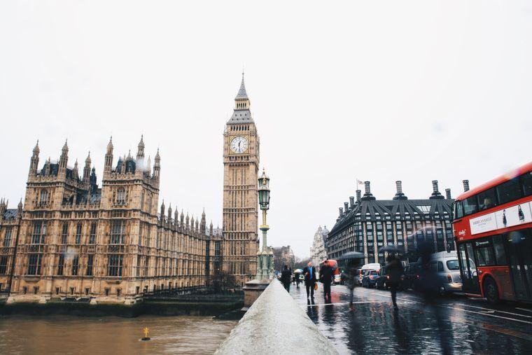 Roter Doppeldeckerbus und Fußgänger mit Regenschirmen überqueren eine Brücke vor dem Big Ben in London, England.