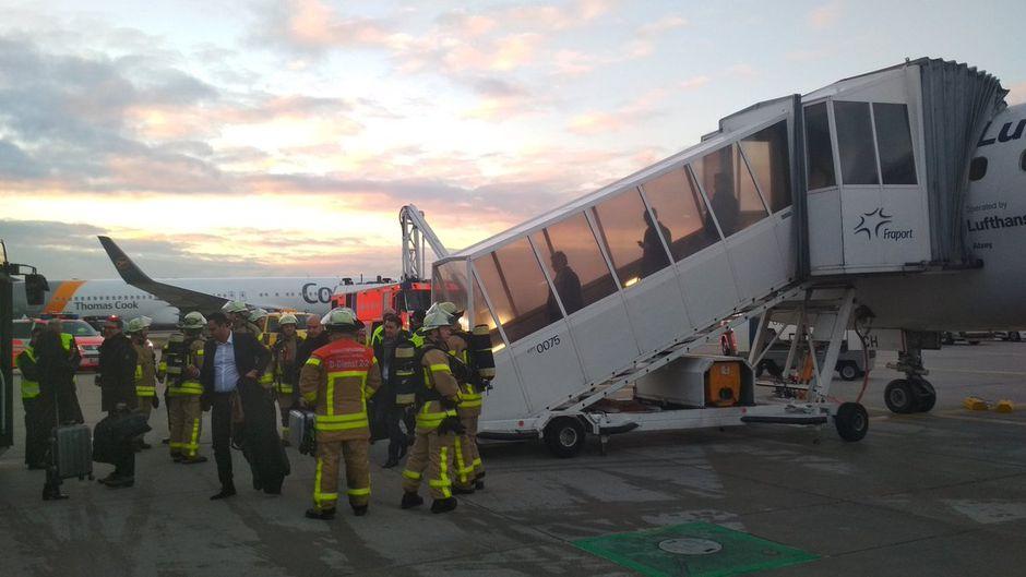 Feuerwehrmänner und Passagiere stehen vor einem Lufthansa-Flugzeug am Flughafen Frankfurt.