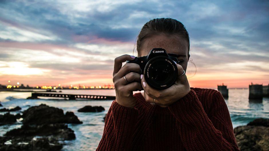 Frau mit Kamera im Urlaub am Meer bei Sonnenuntergang.