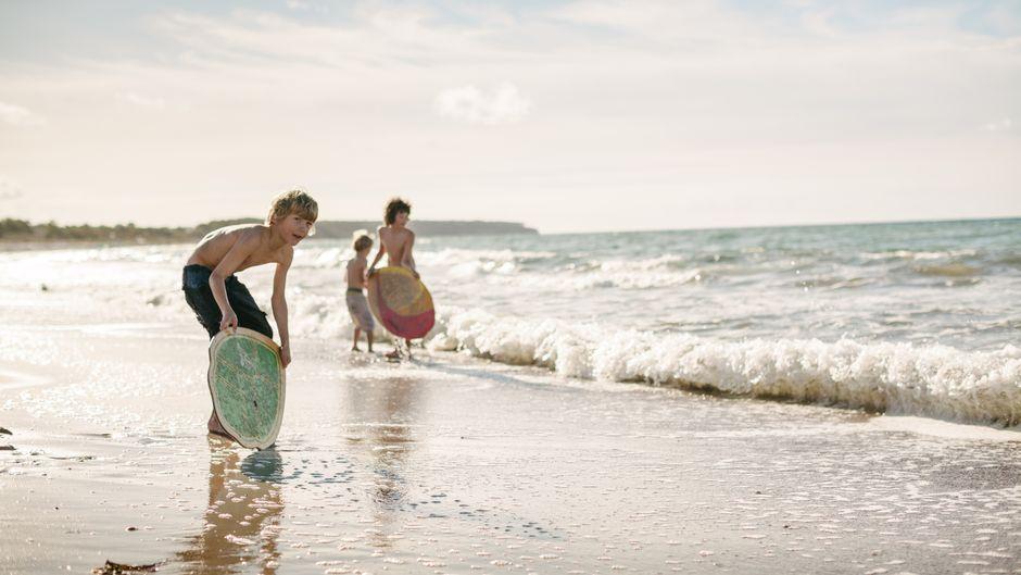 Kinder mit Skimboards am Ostseestrand