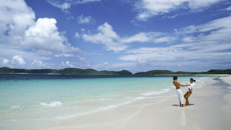 Ein Pärchen genießt die Zeit am Strand von Whitehaven auf den Whitsunday Islands.