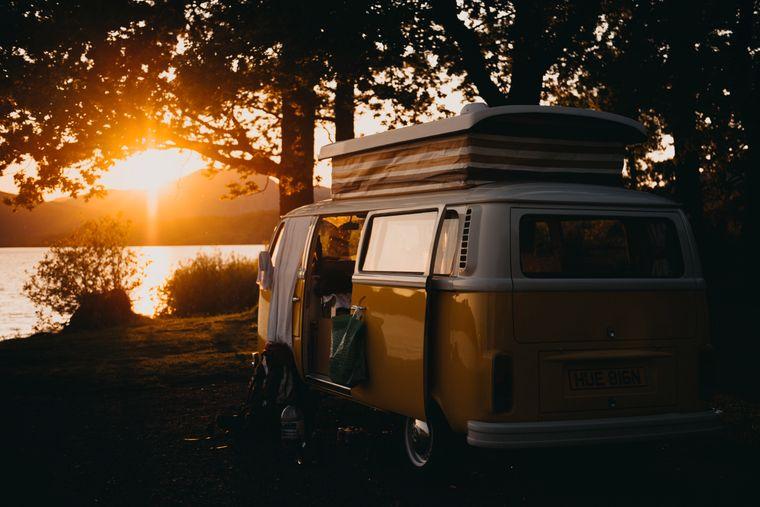 Ein orangefarbener Campervan steht im Sonnenuntergang an einem See.