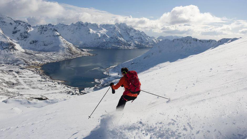Skifahrer bei der Abfahrt mit Blick auf einen Fjord.