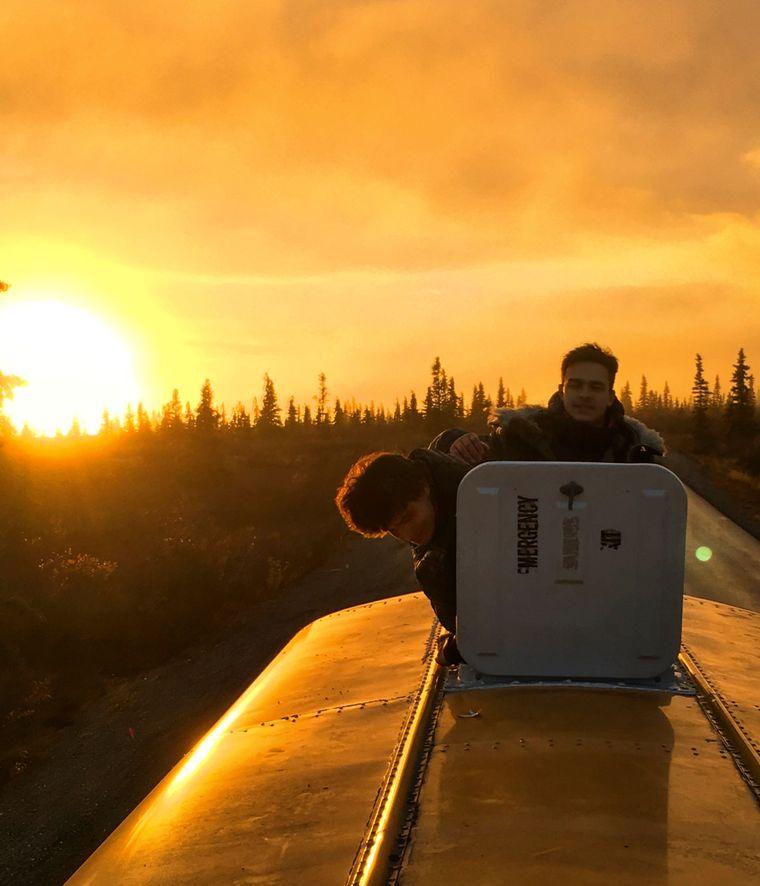 Zwei Jungs stehen auf dem Schulbus in Alaska und schauen in die aufgehende Sonne.