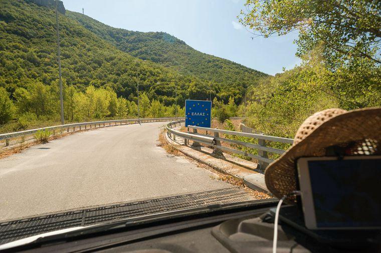 Blick aus einem Fahrzeug auf eine kleine Strasse , wo ein griechisches EU Schild die Landesgrenze von Albanien nach Griechenland ankündigt. Leskovik (Leskoviku), Kolonja, Albanien. Mit dem Campingbus unterwegs in Albanien *** View from a vehicle onto a small road, where a Greek EU sign announces the border from Albania to Greece Leskovik Leskoviku , Kolonja, Albania Travelling by camping bus in Albania  imago images / Kickner