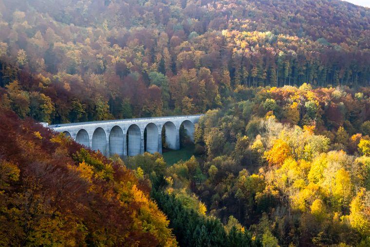 Die Kirche des Ortes Brehm spiegelt sich im Herbst in der Mosel.