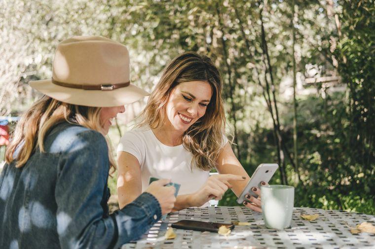 Urlaub planen 2021: Zwei Frauen sitzen in einem Café und schauen aufs Handy. (Symbolfoto)