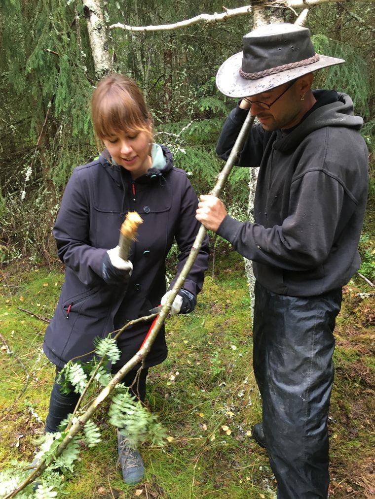 reisereporterin Katharina verwendet ein Stück Holz als Hammer – Hilfe gibt's von Kursteilnehmer Martin Wild.