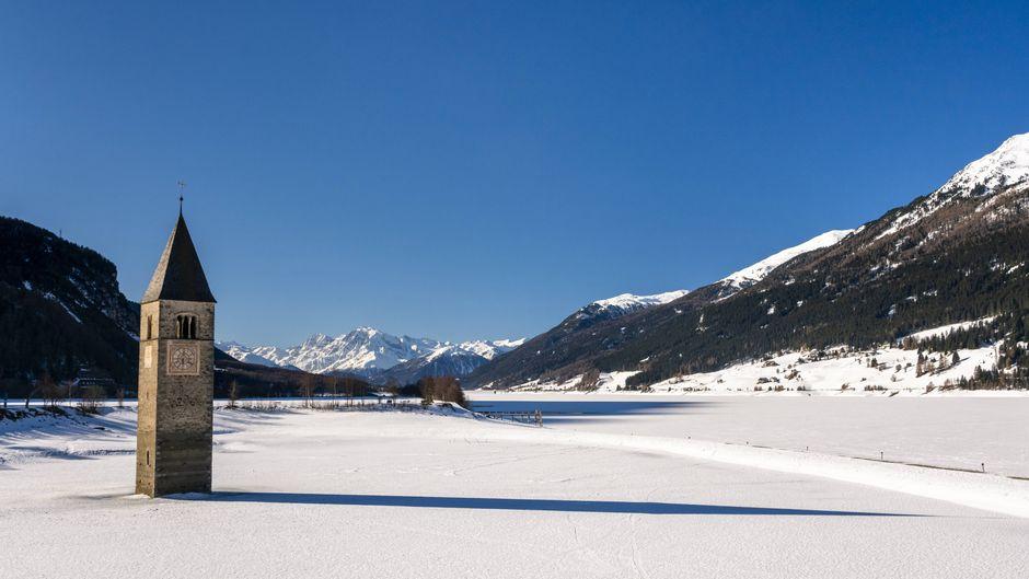 Im Winter, wenn der Reschensee zugefroren ist, sieht es aus, als wäre die Kirche im Schnee versunken. Sie steht aber auf dem Grundes Lago di Resia in Südtirol.
