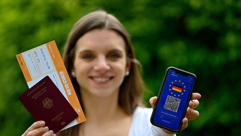 Eine Frau hält ein Smartphone mit digitalem europäischem Impfpass, Reisepass und Boarding Pass in die Kamera.