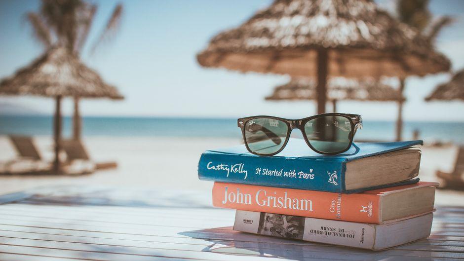 Eine der schönsten Sommerbeschäftigungen: Mit einem guten Buch am Strand liegen.