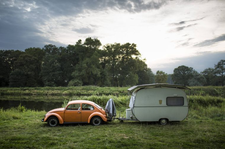Ein VW Kaefer steht mit einem Wohnwagen am Elbufer bei Havelberg