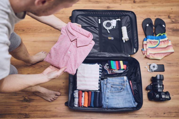 Ein Mann packt seinen Koffer.