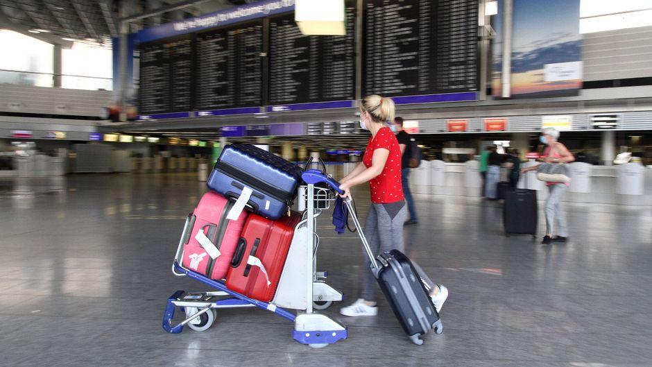 Eine Frau schiebt ihren vollen Gepäckwagen durch den Flughafen Frankfurt – nach der Reise ins Risikogebiet müssen Urlauber bald mindestens fünf Tage in Quarantäne. (Symbolfoto)