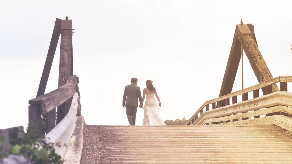 Ein Ehepaar, das auf einer Brücke entlangläuft.