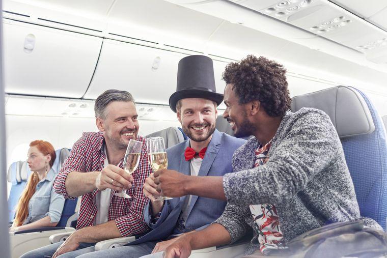 Flugreisende stoßen mit Sekt an.