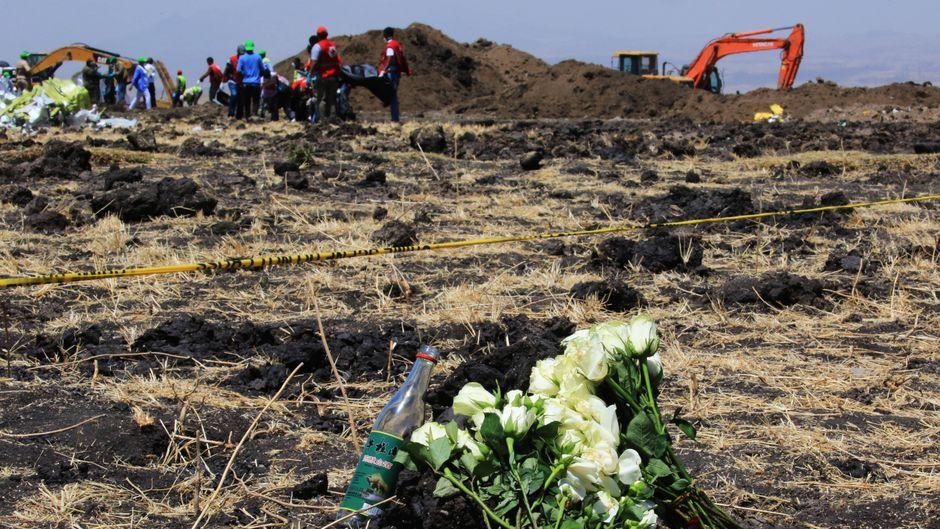 Trauernde gedenken der Verstorbenen an der Absturzstelle der Boeing 737 in Äthiopien mit Blumen.