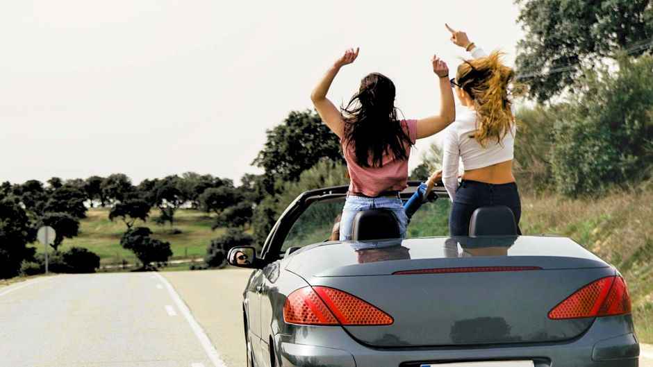 Frauen tanzen im Auto zu Musik.