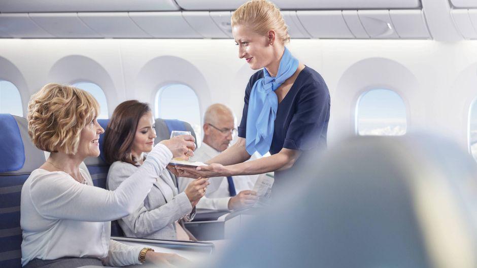 Stewardess serviert Getränk im Flugzeug.