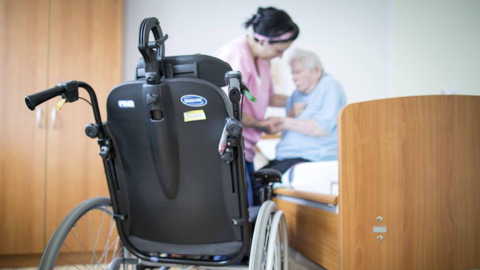Eine Altenpflegerin hilft einer Bewohnerin in einem Altenpflegeheim.