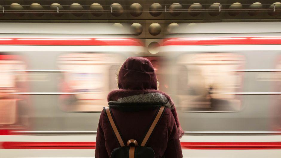 Eine Frau steht am Gleis vor einem vorbeifahrenden Zug.