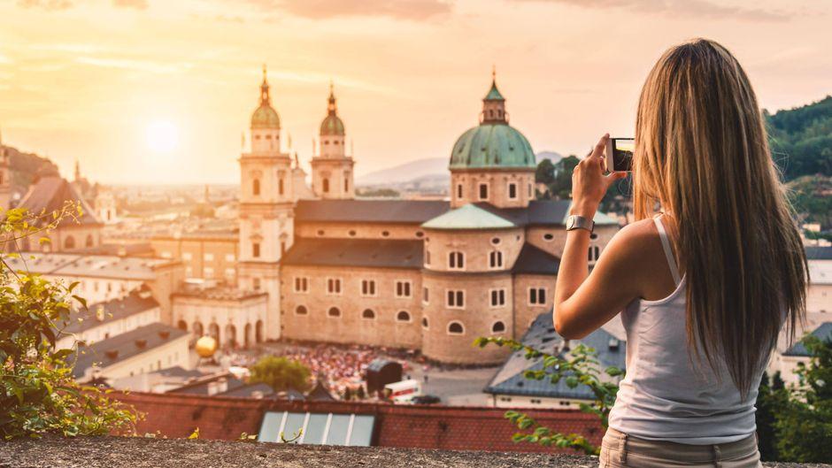 Eine Frau fotografiert den Sonnenuntergang in Salzburg.