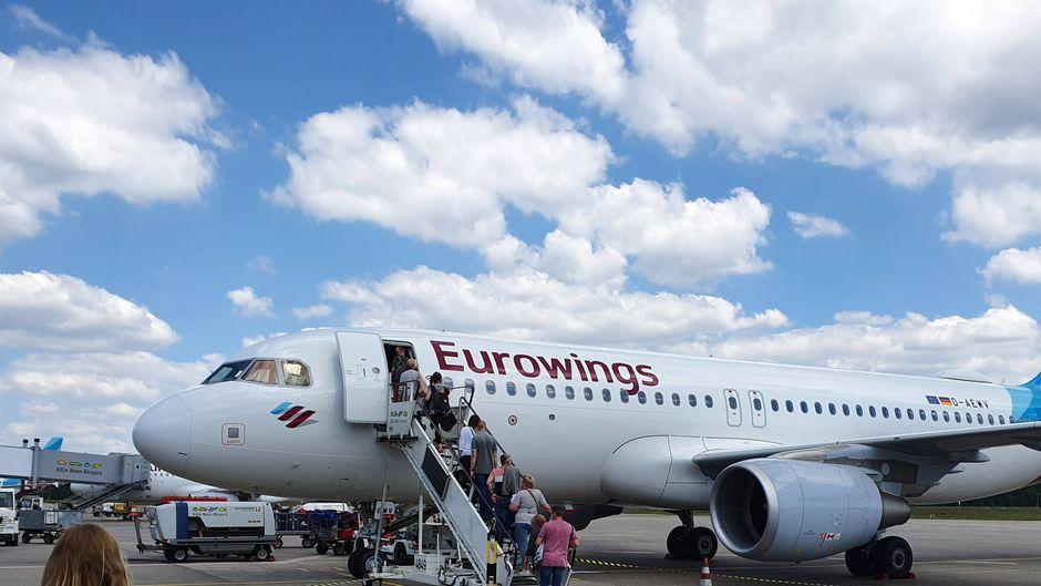 Passagiere mit Rollkoffern steigen aus einem Norwegian-Flugzeug am Flughafen Berlin-Schönefeld.