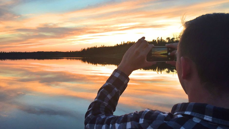Ein Urlauber fotografiert den Sonnenuntergang über einem der Seen im Norden von Ontario, Kanada.