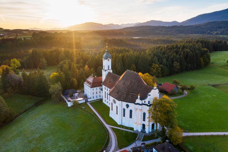 """Die Wallfahrtskirche """"Die Wies"""" in schöner Landschaft bei Sonnenschein."""