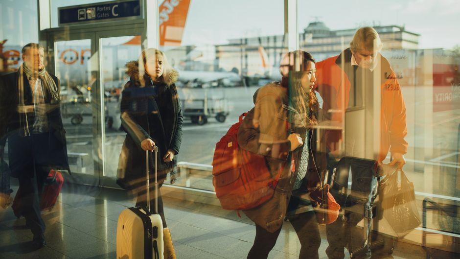 Menschen warten mit ihrem Handgepäck am Gate.