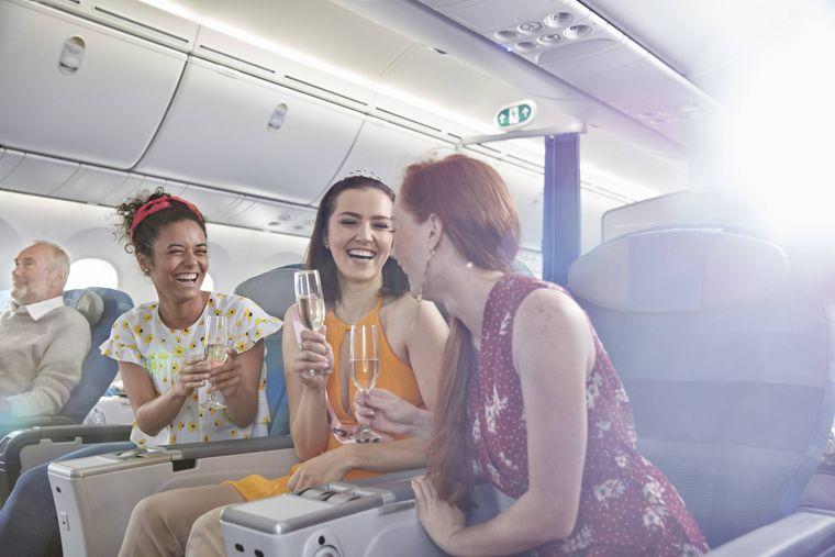 Frauen mit Sekt im Flugzeug.