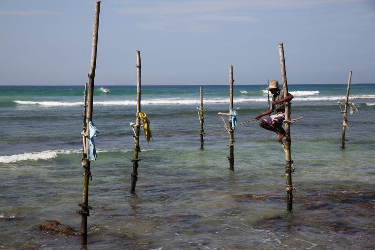 Das Postkartenmotiv Sri Lankas: Ein Fischer, der in Kogala auf seinem Holzstamm sitzt und auf den nächsten Fang wartet.