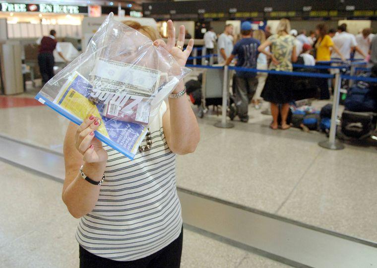 Frau hält Zip-Beutel am Flughafen.