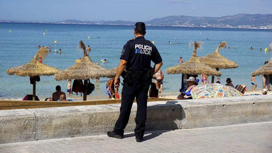 Polizist schaut auf den Strand am Touristen-Hotspot Ballermann in El Arenal. Wird das Reisen risikoreicher?