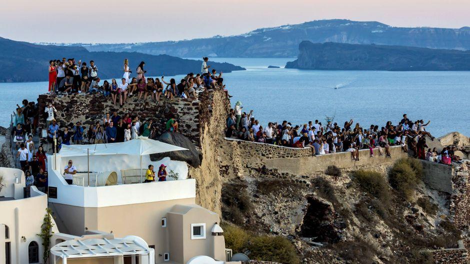 Touristen versammeln sich in Ia auf Santorin im ganzen Dorf, um den Sonnenuntergang zu sehen. Die Insel hat mit den vielen Touristen zu kämpfen.