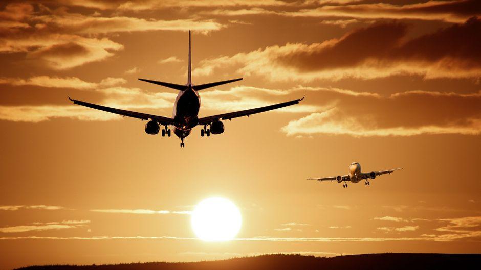 Zwei Flugzeuge kommen sich bei Sonnenuntergang entgegen.