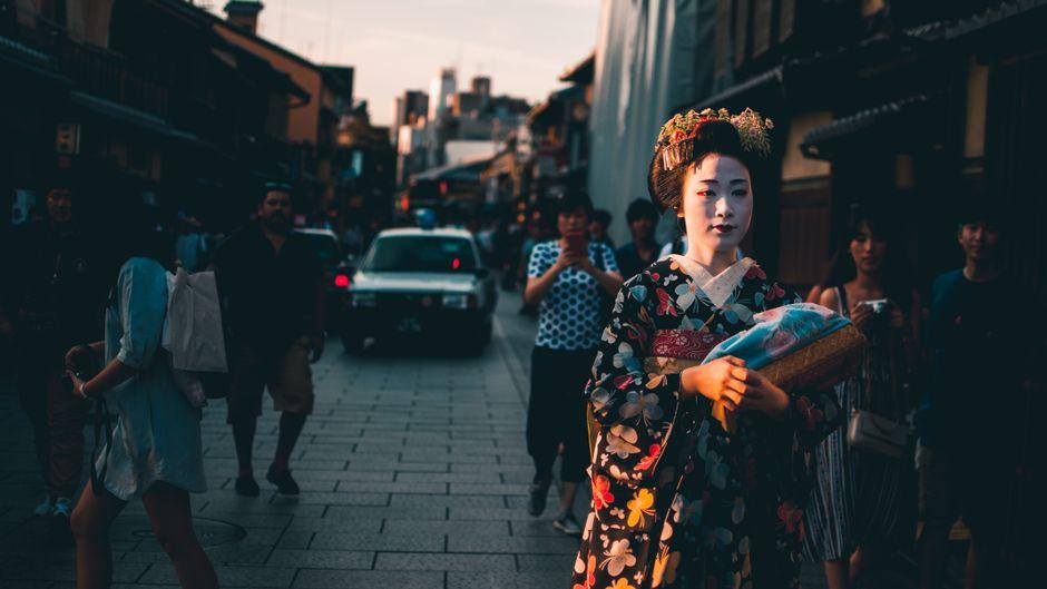 Menschen zücken ihre Handys, um eine Geisha zu fotografieren.