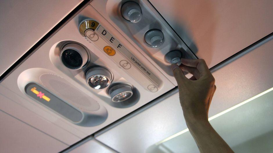 Ein Fluggast stellt im Flugzeug die Lüftung überm Sitz ein.
