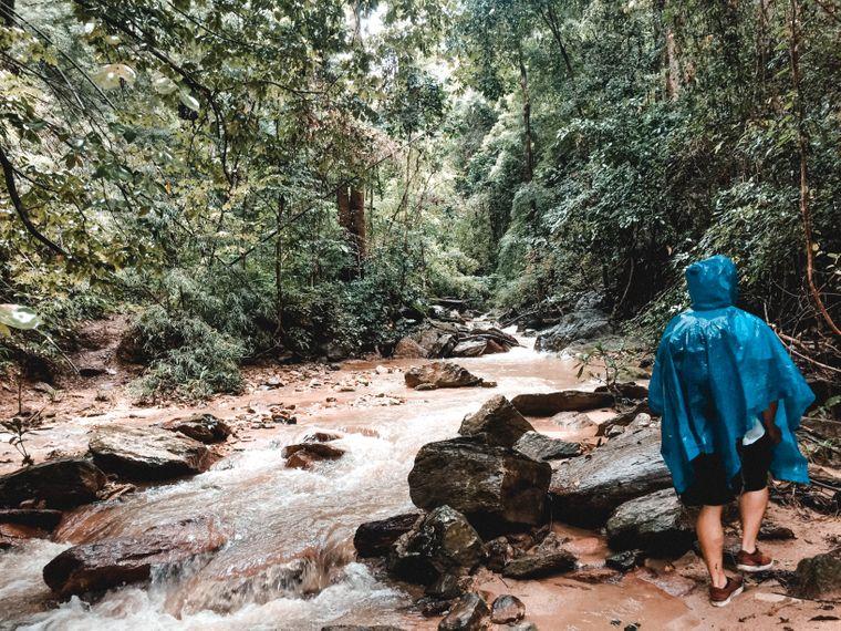 Oleg-Burhanau im Regencape am Bachlauf im Dschungel bei Pai, Thailand.