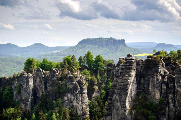 Blick von einem Felsen in der Nationalparkregion Sächsische Schweiz zur Bastei, im Hintergrund erhebt sich der Lilienstein.