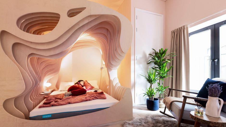 In dem Schlafzimmer des Zed Rooms in London steht ein Bett mit hölzerner Gebärmutterverkleidung.