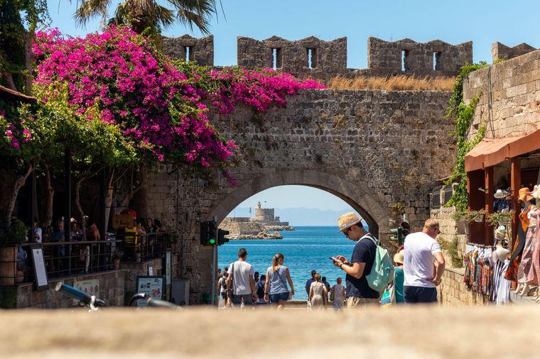 Von der historischen mittelalterlichen Stadt Rhodos aus kannst du den Leuchtturm Agios Nikolaos in der Ferne sehen.