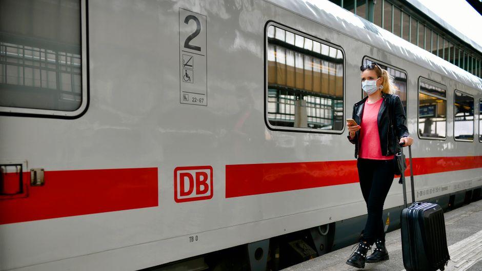 Eine Frau mit Mundschutz wartet auf den Zug. Wie sicher sind Bahnreisen in Corona-Zeiten?