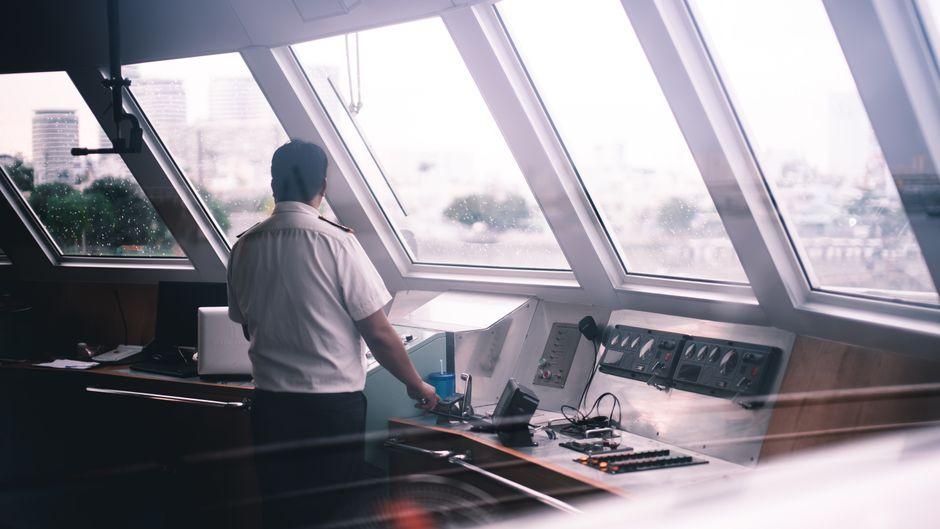 Ein Crewmitglied steht in der Kommandobrücke.