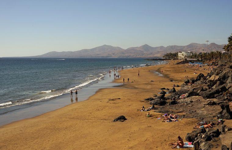 Strand auf Lanzarote mit Vulkanbergen im Hintergrund.